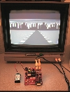 "The XGS Pico Edition PCB running the ""Racer City"" demo on a TV."